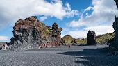 Unidentified Man Walking In Volcanic Lava Rocks At Djupalonssandur Beach In Snaefellsnes Peninsula I poster