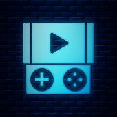 Glowing Neon Portable Video Game Console Icon Isolated On Brick Wall Background. Gamepad Sign. Gamin poster