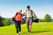 stock photo of golf bag  - Young sportive couple playing golf on a golf course - JPG