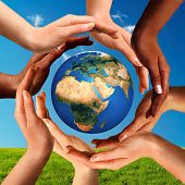 stock photo of earth  - Conceptual peace and cultural diversity symbol of multiracial hands making a circle together around the world the Earth globe on blue sky and green grass background - JPG