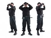Three security guards wearing black uniform looking through binoculars, in three different direction