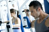 stock photo of abdominal muscle man  - Man and woman at the gym working out - JPG