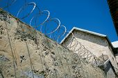 image of stockade  - razor wire attached to the top of a concrete wall in fremantle prison in australia - JPG