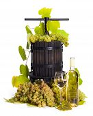 picture of wine-press  - Traditional manual grape pressing utensil with wine and white grape bunch - JPG