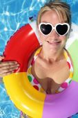 image of summer fun  - Fuky sunglasses on a summer hat with a red tropical hibiscus flower and nice blue pool water - JPG
