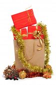 some christmas gifts wrapped with red wrapping paper and with a golden ribbon, in a shopping bag, an