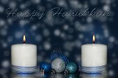 Two candles with blue ribbon and decorations with dreamy background and happy Hanukkah -text in star