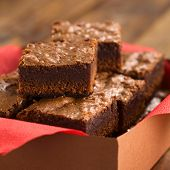 image of brownie  - Freshly baked brownies in a brown paper box with red napkin (Selective Focus Focus on the first brownie on the top)