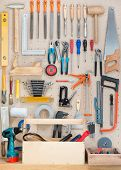 Various carpentry, construction tools hanging on the board.
