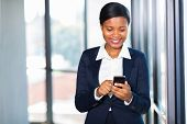 smiling african american businesswoman texting on her smart phone