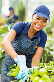 happy young african american nursery worker gardening