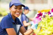 portrait of cute african female florist working in nursery