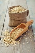 stock photo of oats  - Oat flakes in sac with wooden scoop on wooden background - JPG