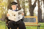 Mature college professor reading newspaper outdoors