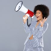 Vivacious beautiful African American woman holding a megaphone in her hand gesturing at the camera w