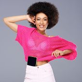 Vivacious chic African American woman with a wild afro hairdo posing in a glamorous see through pink