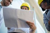 Business woman reading papers wearing hard hat