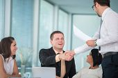 Business men finishing agreement by shaking hands in corporate environment