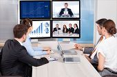 picture of video chat  - Businesspeople Sitting In A Conference Room Looking At Computer Screen - JPG