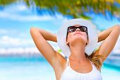 Portrait of young attractive female with hands behind head taking sunbath on the beach, summer vacat