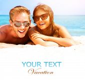 Happy Couple in Sunglasses having fun on the Beach. Summer Vacation. Laughing Family enjoying Nature
