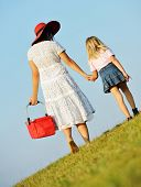 Mother and daughter walking together on beautiful summer meadow enjoying and having fun