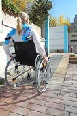stock photo of physically handicapped  - Woman in a wheelchair on a wheelchair ramp - JPG