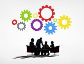 Silhouettes of Business People Having a Meeting and Gears Above