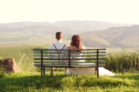 image of zulu  - Bride and groom outside garden wedding on bench with African Natal Midlands mountain scenery background - JPG