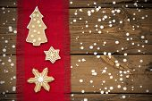 picture of ginger bread  - Three Ginger Bread Cookies on Red Drapery on Wooden Background in the Snow - JPG