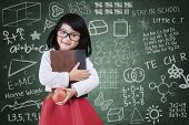 picture of indian apple  - Learning concept with cute little girl holding a book and apple in classsroom - JPG