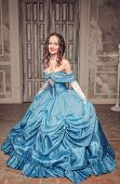 picture of pompous  - Young beautiful medieval woman in long blue dress in the old room - JPG
