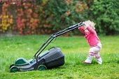 stock photo of work boots  - Cute Curly Baby Girl In Rain Boots Playing With A Big Green Lawn Mower In The Garden On Summer Day - JPG