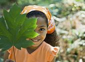 stock photo of pre-adolescent girl  - Mixed Race girl holding leaf in front of face - JPG