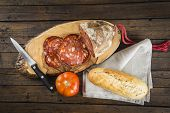stock photo of charcuterie  - Morcon a Spanish sausage like chorizo with bread and tomato on the cutting board - JPG