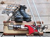 image of ski boots  - old ski boots on a small suitcase full of warm clothes - JPG