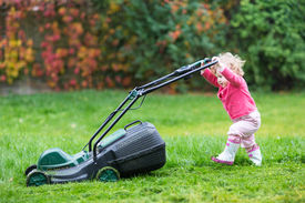 picture of big-girls  - Cute Curly Baby Girl In Rain Boots Playing With A Big Green Lawn Mower In The Garden On Summer Day - JPG