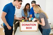 foto of tin man  - Group Of Multiethnic People Holding Tin Can Looking Inside Donation Box - JPG