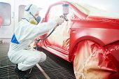 stock photo of vapor  - auto mechanic worker painting a red car in a paint chamber during repair work - JPG