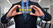 pic of 5s  - Businessman holding five star rating  - JPG