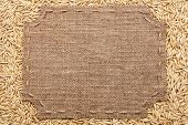 picture of stitches  - Figured frame with burlap and stitches with place for your text lying on oats grains as a background - JPG