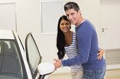 stock photo of showrooms  - Couple holding a car door handles at new car showroom - JPG