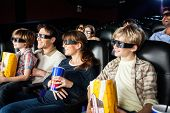 stock photo of watching movie  - Smiling families with snacks watching 3D movie in cinema theater - JPG