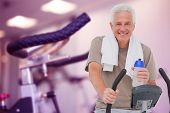 picture of exercise bike  - Senior man on exercise bike against row of exercise bikes focus on foreground - JPG