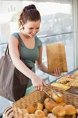 stock photo of bread rolls  - Pretty brunette picking out bread roll at the bakery - JPG