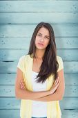 stock photo of frown  - Frowning casual woman looking at camera against wooden planks - JPG