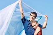 stock photo of flutter  - Young pair with white scarf fluttering on wind against blue sky - JPG