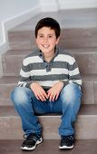 stock photo of preteen  - Preteen boy sitting on the stairs at home - JPG