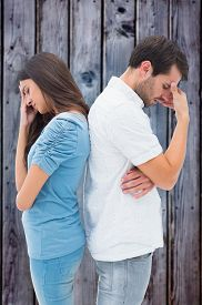 foto of not talking  - Upset couple not talking to each other after fight against grey wooden planks - JPG