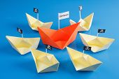 stock photo of pirate flag  - Paper origami ship and several pirate Vessel with black flag Jolly Roger